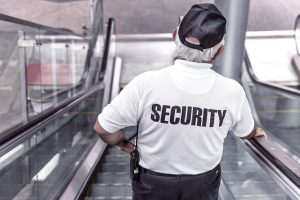 Security guard on escalators, wearing cap, offering security